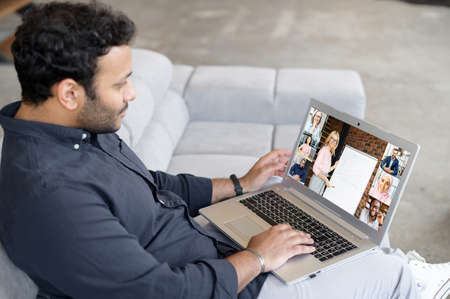 Indian male student studying online, using laptop computer for video connect with teacher, mentor, diverse classmates on the screen. Hispanic multiracial businessman involved webinar, training Banque d'images