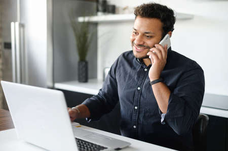 Indian guy talks on the smartphone and using laptop computer staying at home and working on the distance, smiling hindu man has phone conversation looking at the computer screen