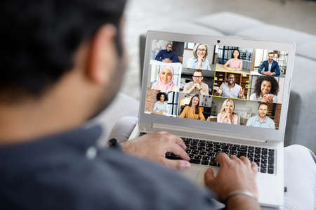 Young businessman using laptop app for video connect with colleagues, takes part in video conference, screen with many diverse people involved in video meeting,group of multiracial coworkers on screen