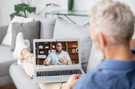 Virtual meeting concept. African-American man on the laptop screen is holding video conference, talking and explaining something to senior grey haired man, two male business partners connect via video Banque d'images