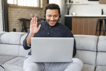 Indian businessman wearing headset using laptop computer for connection with colleagues, customers, hispanic mixed-race man waving into webcam, working remotely, staying at home