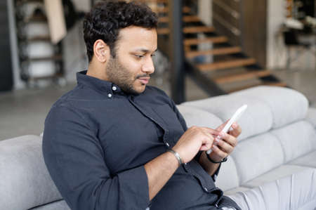 Side view indian young businessman using smartphone sitting on the couch at home. Smiling hispanic guy texting and messaging on phone, sharing news in social networks. Hindu man holding mobile phone