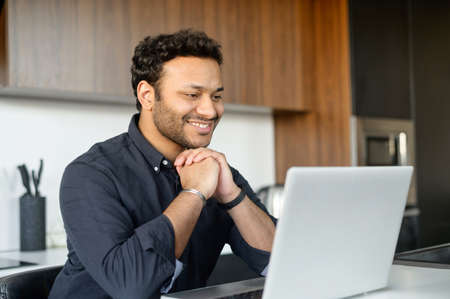 Positive hindu man in smart casual shirt using laptop sitting at the desk in the kitchen, young indian male student watching webinars, educational courses, learning on the distance