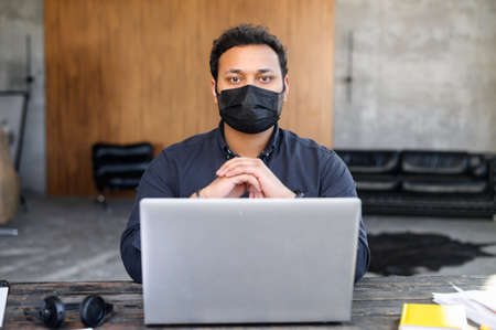 Hindu mixed-race male employee wearing protective face mask working in the office space, looks at the camera. Measure for staying in safe of office staff from viral diseases during pandemic period Banque d'images