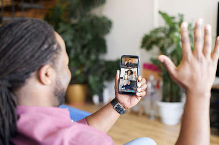 Group video call on the smartphone. An African-American man using mobile app for video connection with diverse group of colleagues or friends, waving and greeting Banque d'images