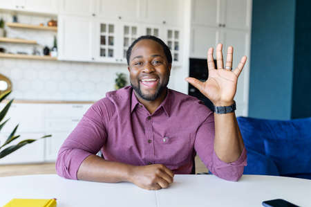 Glad to see you. African-American guy looks at the camera and waving hello, greeting online interloculor or participants of virtual meeting, involved in video call, virtual conference, webcam view