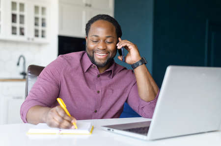 Cheerful and happy African-American male entrepreneur using laptop computer, talking on the smartphone and writes notes sitting at the desk at home, has phone conversation and makes schedule