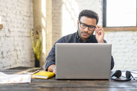 Inteligente indian mixed race man typing on the keyboard, male in smart casual shirt and stylish eyewear using laptop in modern loft office