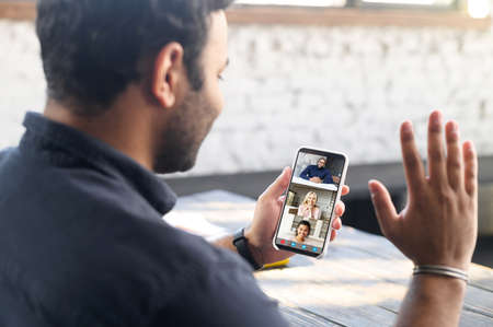 Indian guy using mobile app for video connection, holding smartphone and waving to online interlocutor, happy hindu guy enjoying chatting via video call, staying in touch with family on the distance
