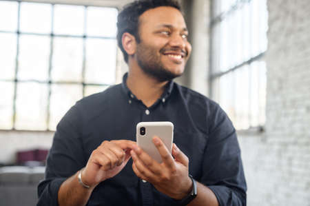 Smiling indian mixed race man with a smartphone in hand looks away standing indoor