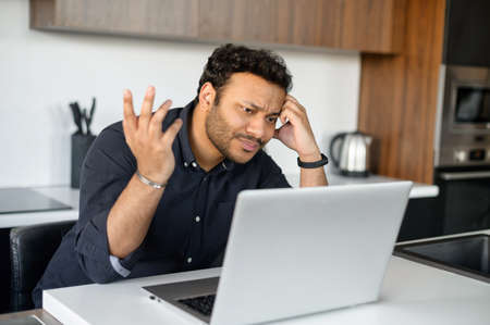 Confused indian man in smart casual shirt looking at the laptop screen, misunderstanding what happened, issues with a project or system error on the computer