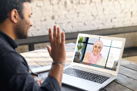 Back view multiracial middle-eastern man using mobile computer app for video meeting with female friend or employee wearing hijab, guy using laptop, talking online with islamic woman. Video call Banque d'images