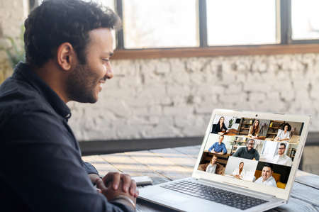 Morning meeting on the distance. Back view over shoulder of hindu guy to the laptop screen with a lot of diverse people on it, work team brainstorming, discussing together, virtual meeting colleagues