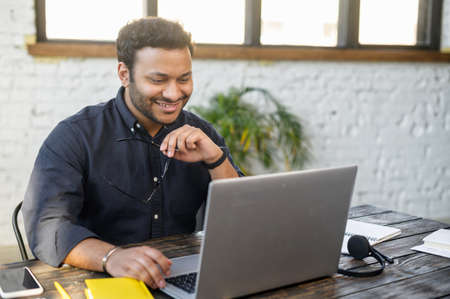 Optimistic indian mixed race man using laptop, male employee in smart casual shirt take off eyewear, watching at the monitor and smiling