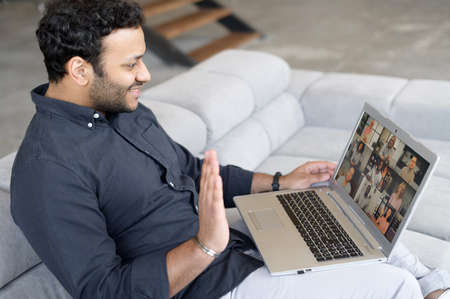 Young indian man using laptop for virtual meeting with colleagues, brainstorming with a multiracial team online, group of diverse people on the screen. App for video communication, video call concept