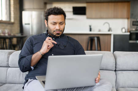 Thoughtful indian man using laptop sitting on the couch at home, a hindu guy looks at the screen, looking for new sturtup idea, solving difficalt tasks, planning future
