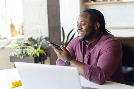 Smiling African-American man with locks hair sending voice message sitting at home office, positive black guy in casual shirt using voice recognition app, recording audio report, side view