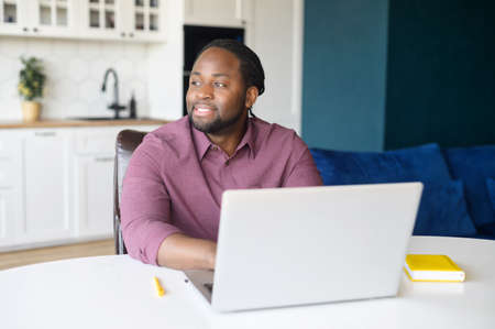 Serene African-American businessman using laptop for remote work, sitting at the desk and looks away, waiting for inspiration and news ideas, positive black guy typing sitting in the kitchen