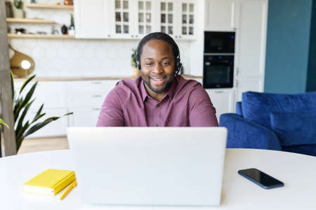 Guy in wirelessheadset using laptop sitting in the kitchen home. Remote work concept Banque d'images