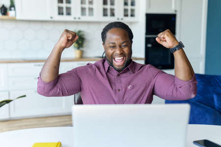 Lucky overjoyed African-American man staring at laptop monitor with happily face expression, screaming yes, received good news or deal, black man celebrating project finished or winning in video game Banque d'images