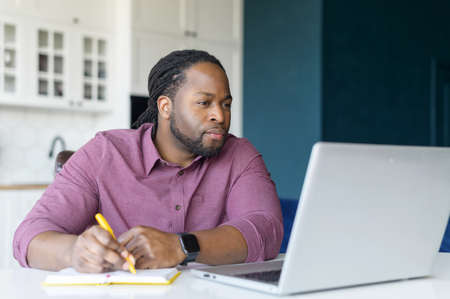Serious and focused African-American guy watching webinars on the laptop and taking notes, studying remotely from home, writing down some important things, working on new project