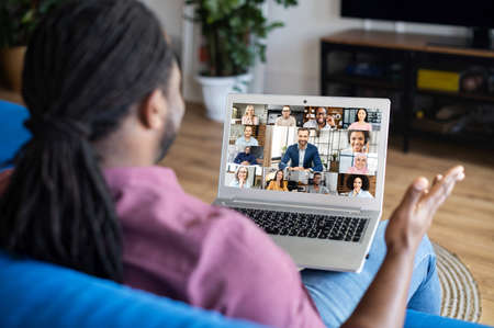 Group of diverse colleagues talks via video call. African-American man with locks hairstyle using laptop computer for virtual meeting with coworkers, business partners, peoples talk on the screen Banque d'images