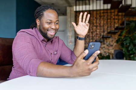 Happy African-American guy holding smartphone and gesturing hello, making video call, using mobile app for video connection sitting at home Banque d'images