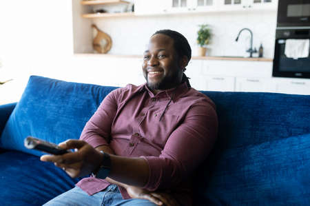 Smiling African-American man with dreadlocks holding TV remote controller, black guy watching television shows, enjoying favorite series, resting on the couch at home, weekend leisure