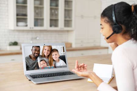 Cheerful smiling African-American female student using laptop for video connect with family on the distance, young woman talks online Banque d'images
