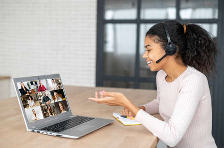 Virtual video conference, online meeting with a many employees together. A young African woman wearing headset is communicating via video call with coworkers, many people on the laptop screen