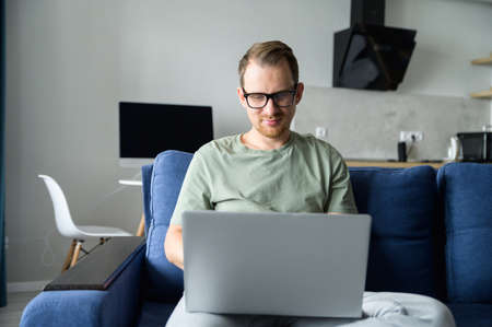 Clever freelancer using laptop for remote work from home. A handsome bearded guy websurfing, sends and answering emails, develops software sittin on the couch at home. Intelligent man works remotely
