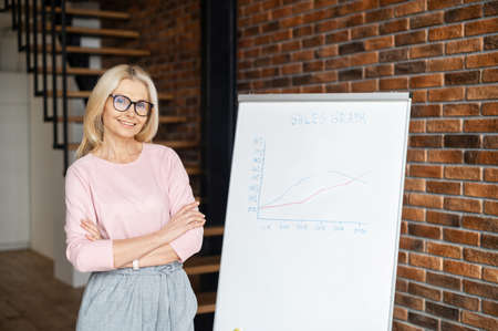 High-skilled business coach with arms crossed stands near whiteboard with graphs. Smiling middle-aged woman in eyeglasses looks at the camera, conducts online webinar, giving training Banque d'images