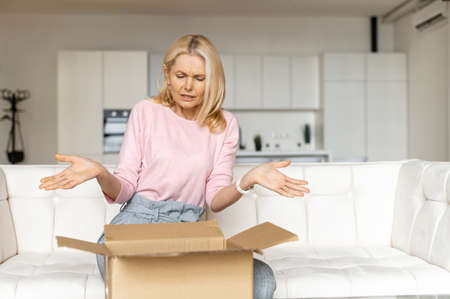 Confused female customer received wrong order. Disappointed middle-aged blonde woman sits on the couch and unpacking box with online order with frustrated face expression Banque d'images