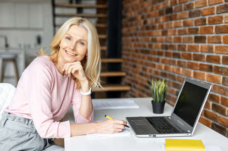 Positive charming mature blonde businesswoman sitting at the desk in front of laptop, working on a project. Freelancer enjoying remote work from home, looks at the camera and smiling