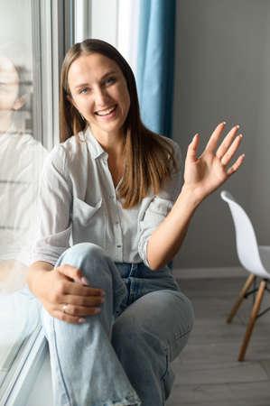 Friendly adorable young woman joyfully waving at the camera, smiling and saying hi