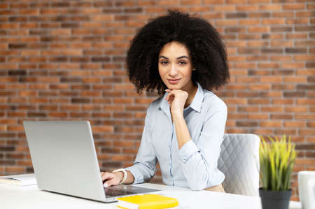 Smiling intelligent biracial woman with Afro hairstyle using laptop for work online sitting at the desk and looks at camera in the coworking space, female freelancer typing on the keyboard Banque d'images
