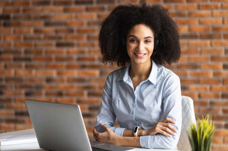 Successful biracial woman wearing smart casual shirt stands in confident pose with arms crossed, confident mixed-race female entrepreneur in home office looks at the camera Banque d'images