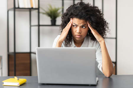 Tired African-American businesswoman in casual shirt sitting at the desk in front of laptop, upset mixed-race female office employee feels bad and burnout