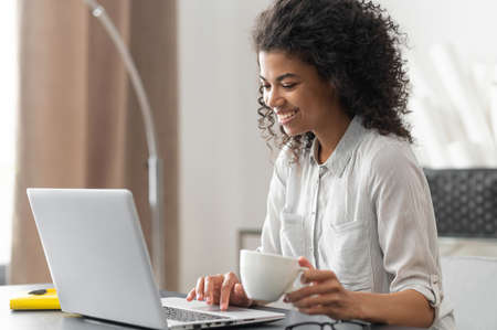 Smiling young cheerful African American woman with Afro hairstyle enjoying morning coffee while watching video news on the laptop.