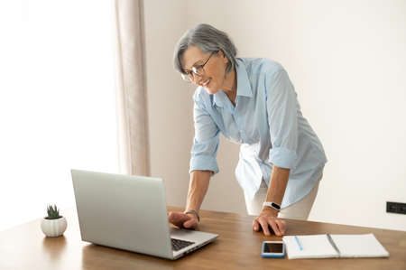 Senior middle-aged businesswoman wearing glasses, looking at the laptop screen, waiting to get connected to online conference or webinar.