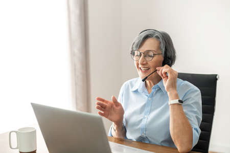 Grey-headed mature senior female office worker sitting at the desk with a laptop, wearing glasses, headset. Banque d'images