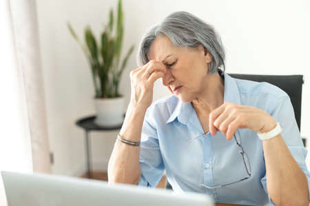 Tired and overworked stressed mature woman working on laptop at home indoor, female teacher feeling exhausted after lecturing students online, touching eyes. Banque d'images