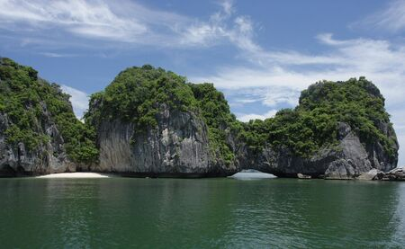 Island in Halong Bay with beach and cave, near Cat Ba photo