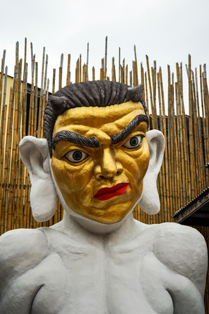 passtime: Statue of a sitting demon in cafe on Rambuttri road, Bangkok, Thailand Stock Photo
