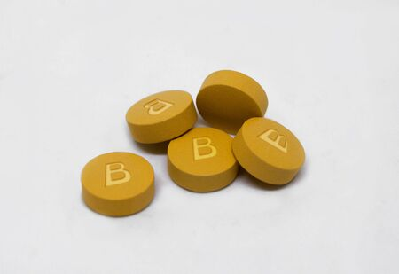 Vitamin B pills to create energy and red blood cells with text isolated on white background Фото со стока