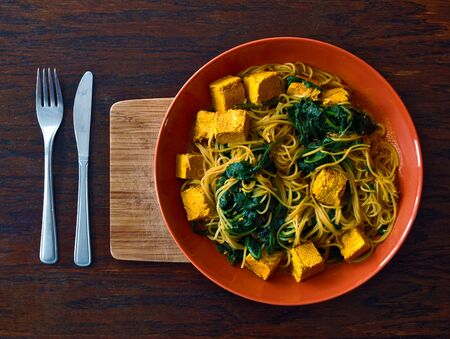 Vegetarian or vegan Indian food with noodles, spinach and tofu in the orange plate with wooden cutting board and cutlery. Suitable as a photo for a vegan or vegetarian restaurant. Фото со стока