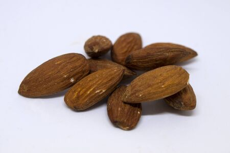 Group of almonds isolated on white background. Close up photo. Type of very good, expensive and healthy nuts. Фото со стока