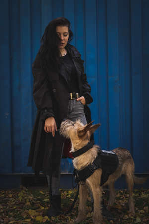 A girl with a dog. Brunette in a black cloak on a blue background. Stock Photo
