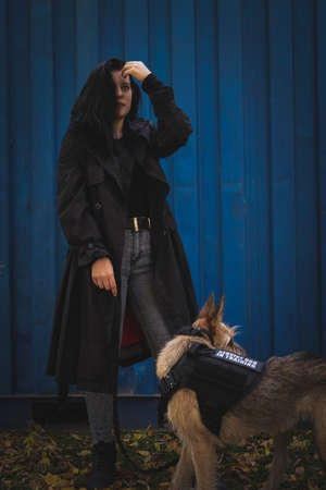 A girl with a dog. Brunette in a black cloak on a blue background.