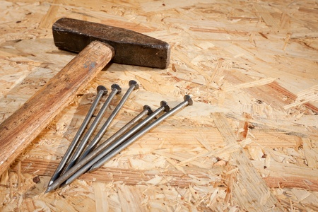Hammer and nails over hardboard background